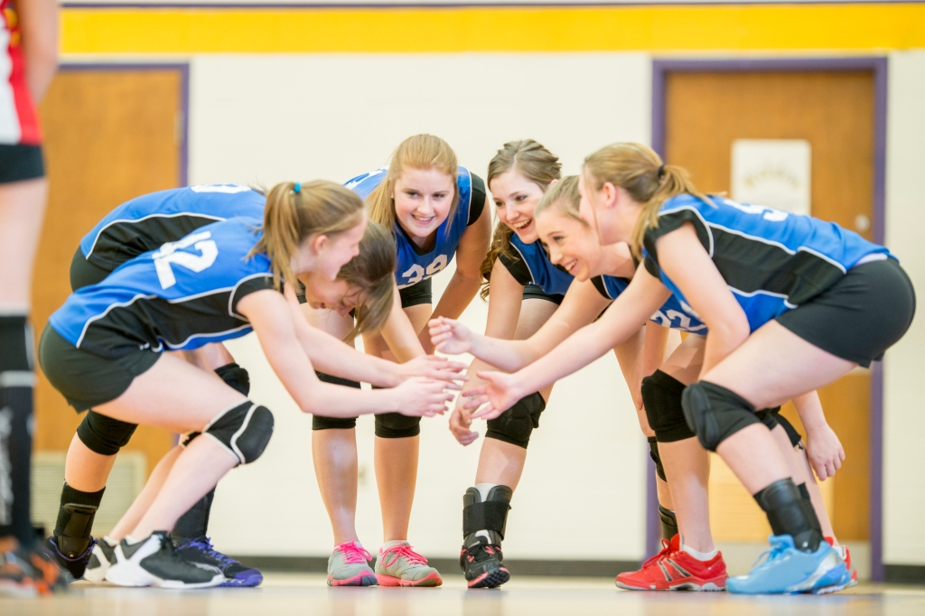 Volleyball team celebrating after coach used a tablet to show the lesson plan